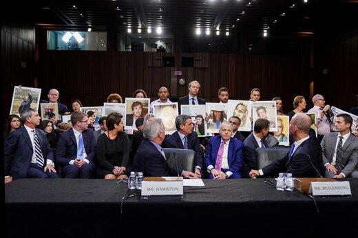 جان همیلتون و دنیس مویلنبرگ، سرمهندسان شرکت بوئینگ، در جلسه پاسخ به پرسشهای قانونگذاران در کنگره آمریکا، به خانواده های قربانیان دو سقوط بوئینگ ۷۳۷ مکس که عکس جانباختگانشان را در دست دارند نگاه میکنند