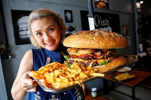 یک زن بزرگترین همبرگر تایلند به وزن 6 کیلوگرم را قبل از شروع مسابقه خوردنش در رستورانی در بانکوک در دست گرفته است