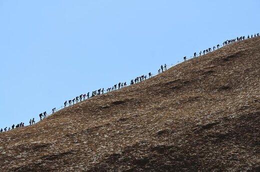 صعود گردشگران از تپه اولورو در پارک ملی منطقه شمالی استرالیا در آخرین روزی که مردم اجازه صعود از این تپه را داشتند