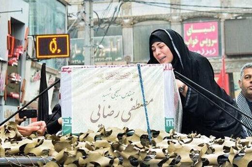 عکس | بیتابی خواهر شهید کنار تابوت برادر