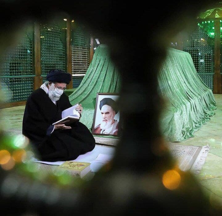 عکسی از قرآن خواندن رهبر انقلاب بر سر مزار امام خمینی(ره)
